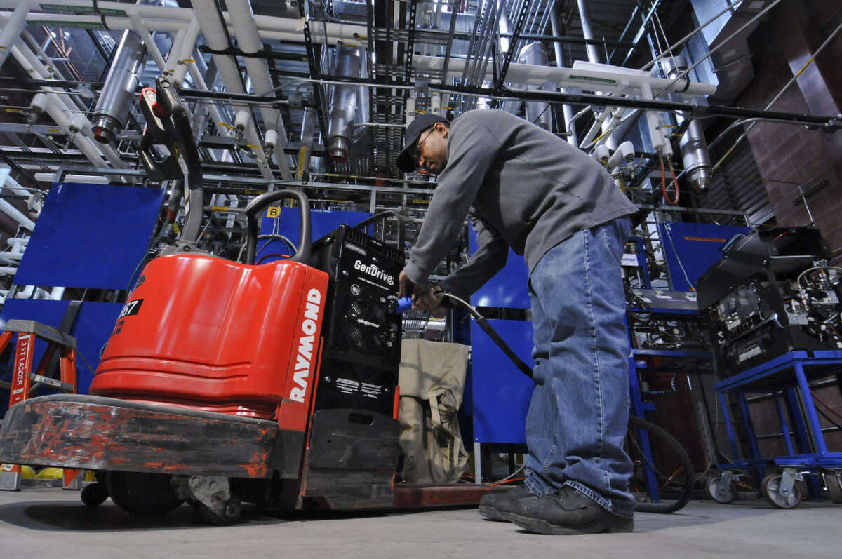Plug Power production technician Evan Paul fills a lift's Gen Drive Class 3 fuel cell with hydrogen in a lab at their plant on Wednesday April 25, 2012 in Latham, NY. Hydrogen is taken from natural gas. Low natural gas prices are giving manufacturers a boost in competitiveness and in their bottom line (Philip Kamrass / Times Union )
