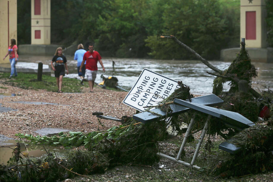 Residents inspect the damage and debris caused by the Guadalupe River and Comal rivers flowing over their banks in New Braunfels  on October 31, 2013. Photo: TOM REEL