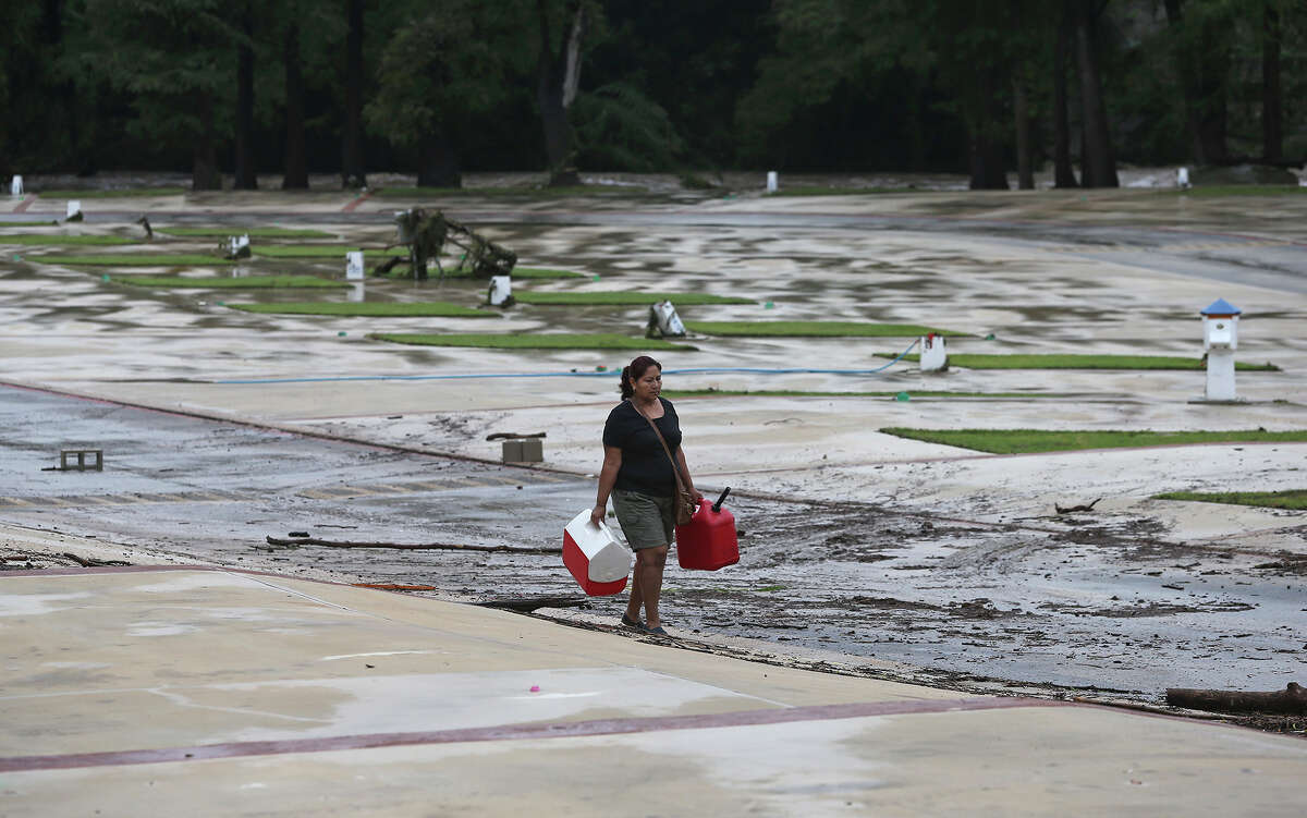A woman collects articles strewn over the campground at River Ranch RV Park after the Guadalupe River and Comal rivers flow over their banks in New Braunfels on October 31, 2013.