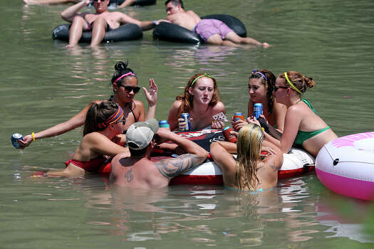 A group from Austin plays cards and enjoys beverages in the water as  enthusiasts cool down in the Guadalupe River near New Braunfels on July 6, 2013. Photo: TOM REEL