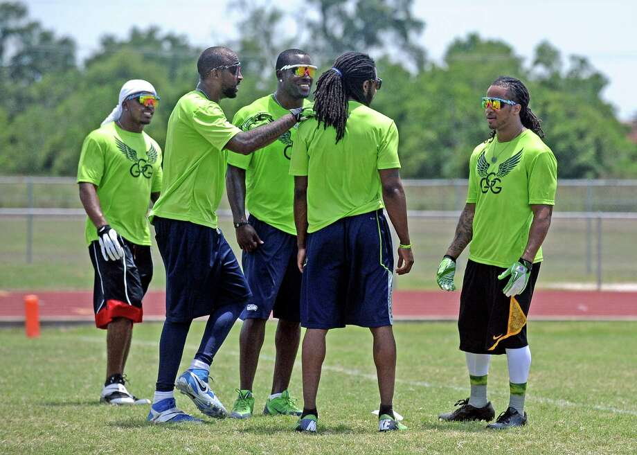 Earl Thomas, right, talks with teammates during Earl Thomas III second annual football camp 7-on7 football game at West Orange-Stark High School on Saturday, June 29, 2013. Photo taken: Randy Edwards/The Enterprise Photo: Randy Edwards