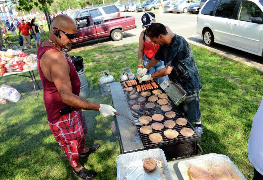 Angel Baez cooks up burgers and hot dogs for the Bridgeport Caribe Youth Leaders' Caribe Day event at Seaside Park in Bridgeport, Conn. on Saturday June 29, 2013. Photo: Christian Abraham / Connecticut Post