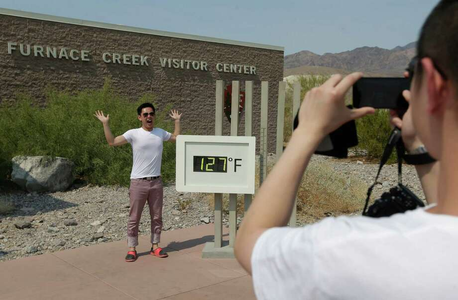 Cheng Jia, of China, right, takes a picture of Yongxin Yan by a digital thermometer at the Furnace Creek Vistitor Center in Death Vally National Park Friday, June 28, 2013 in Furnace Creek, Calif. Excessive heat warnings will continue for much of the Desert Southwest as building high pressure triggers major warming in eastern California, Nevada, and Arizona. Photo: Chris Carlson, Associated Press / AP