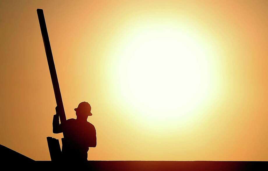 A construction worker is shown atop a roof at sunrise to beat daytime high temperatures, Thursday, June 27, 2013 in Queen Creek, Ariz. Excessive heat warnings will continue for much of the Desert Southwest as building high pressure triggers major warming in eastern California, Nevada, and Arizona. Dangerously hot temperatures are expected across the Arizona deserts throughout the week with a high of 118 by Friday. Photo: Matt York, Associated Press / AP