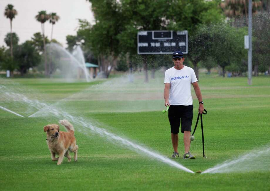 Chris Jolley, right, of Scottsdale, runs his dog Logan through sprinklers at a local park on Saturday, June 29, 2013, in Scottsdale. Excessive heat warnings will continue for much of the Desert Southwest as building high pressure triggers major warming in eastern California, Nevada, and Arizona. Temperature's are expected to get as high as 118 degrees. Photo: Rick Scuteri, Associated Press / FR157181 AP