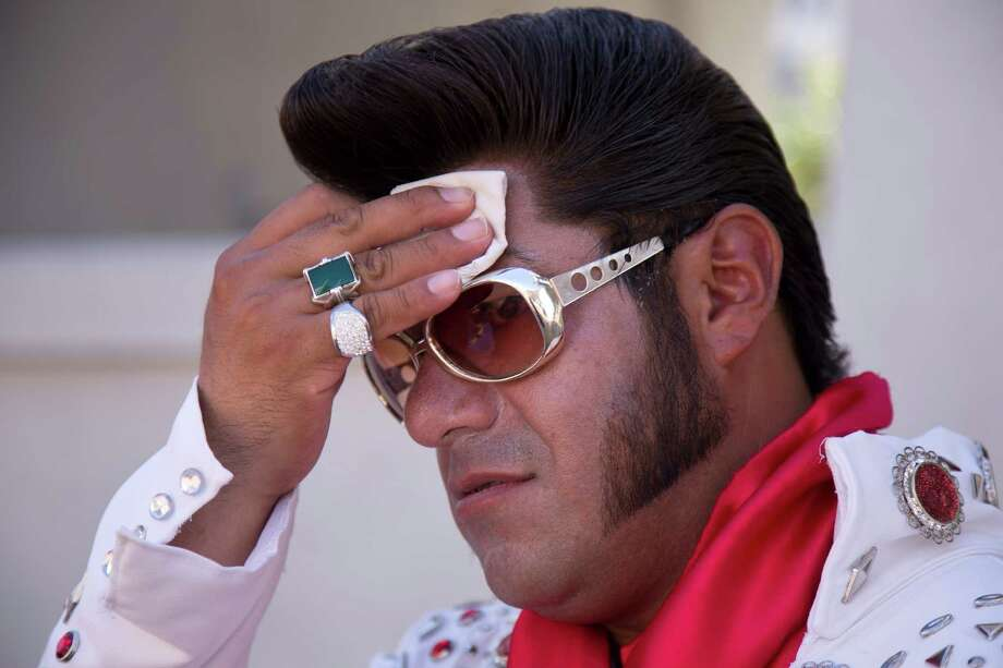 "Elvis impersonator Cristian Morales wipes sweat from his brow while standing out on The Strip posing for photos with tourists, Thursday, June 27, 2013 in Las Vegas. Morales preferred to stand out in the 112 degree heat of the day instead of working the cooler evening hours saying ""We'd much rather fight with the sun than fight with the drunk people."" A high pressure system parking over the West is expected to bring temperatures this weekend and into next week that are extreme even for a region used to baking during the summer. Photo: Julie Jacobson, Associated Press / AP"
