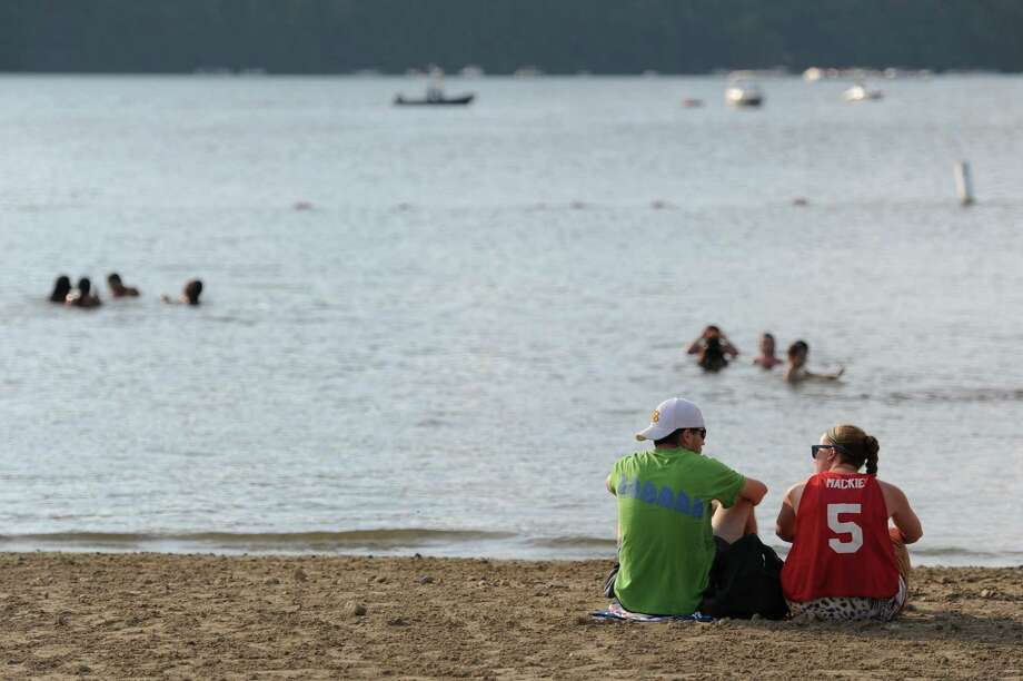 Drew Woods, of Newtown, and Macaire Jones, of Danbury, sit on the beach before the July 4th fireworks display at Candlewood Lake in Danbury, Conn. on Saturday, June 29, 2013. Photo: Tyler Sizemore / The News-Times