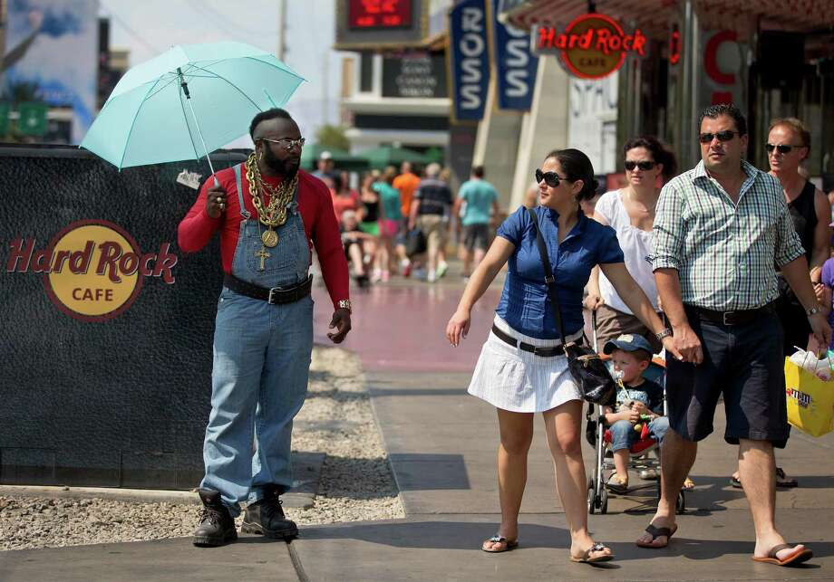 A Mr. T impersonator shades himself from the sun with an umbrella while waiting for requests for photos from tourists along The Strip, Friday, June 28, 2013 in Las Vegas. A blazing heat wave expected to send the mercury soaring to nearly 120 degrees in Phoenix and Las Vegas settled over the West on Friday, threatening to ground airliners and raising fears that people and pets will get burned on the scalding pavement. Photo: Julie Jacobson, Associated Press / AP