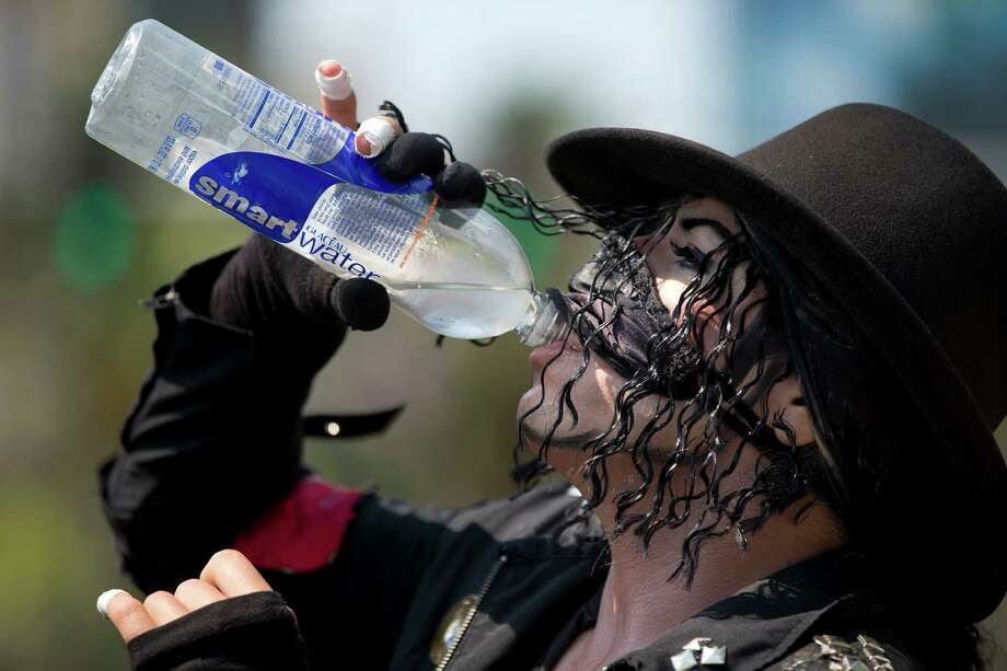 Michael Jackson impersonator Juan Carlos Gomez drinks some water as he takes a break from posing for photos with tourists along The Strip, Friday, June 28, 2013 in Las Vegas.   A blazing heat wave expected to send the mercury soaring to nearly 120 degrees in Phoenix and Las Vegas settled over the West on Friday, threatening to ground airliners and raising fears that people and pets will get burned on the scalding pavement. Photo: Julie Jacobson, Associated Press / AP