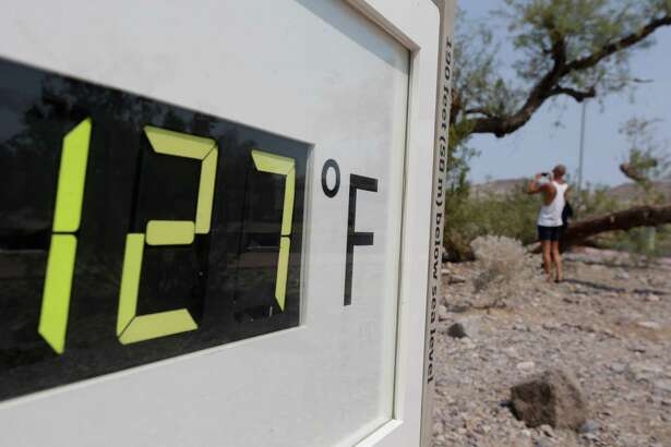 A visitor to the Furnace Creek Vistitor Center walks by a digital thermometer in Death Vally National Park Friday, June 28, 2013 in Furnace Creek, Calif. Excessive heat warnings will continue for much of the Desert Southwest as building high pressure triggers major warming in eastern California, Nevada, and Arizona.