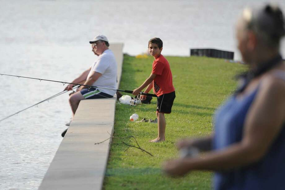 Ryan Pecore, 8, of Danbury, fishes with his grandmother, Carol Pecore, right, and Danbury residents Mike and Cecelia Waldo, left, before the July 4th fireworks display at Candlewood Lake in Danbury, Conn. on Saturday, June 29, 2013. Photo: Tyler Sizemore / The News-Times