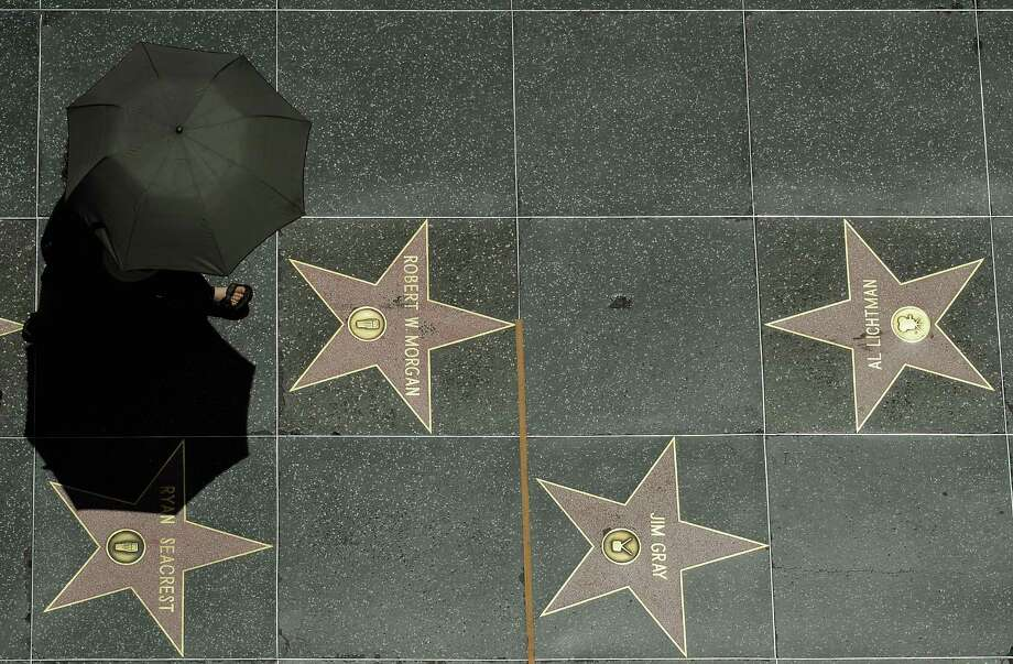 A tourist holding an umbrella to shield herself from the sun walks on Hollywood Walk of Fame stars during a major heat wave in Southern California on June 28, 2013 in downtown Los Angeles, California. Temperatures are expected to be in the triple digits in most areas of Southern California. According to the national Weather Service, the heat wave is expected to linger into early next week prompting heat advisories and opening of cooling centers. Photo: Kevork Djansezian, Getty Images / 2013 Getty Images