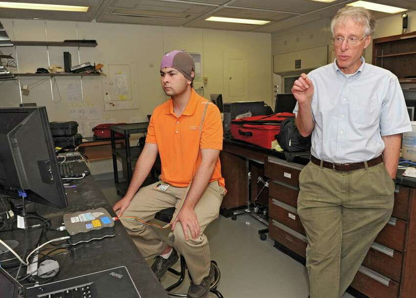 Andrew Wilkinsen wears an electro-cap to write a message with his brain waves while sitting in front of a computer at The Laboratory of Neural Injury and Repair at the Wadsworth Center on Thursday, June 27, 2013 in Albany, N.Y. Lab chief, Jonathan Wolpaw, M.D. explains the process at right. (Lori Van Buren / Times Union)