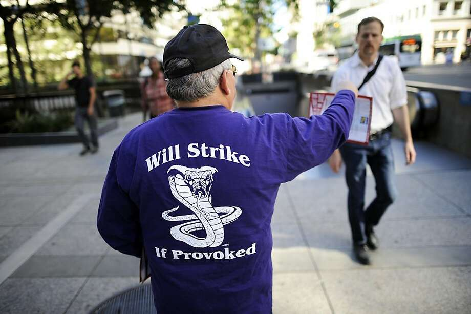 BART electrician and SEIU member Jose Riggio hands out flyers to BART passengers at the entrance to the 12th Street Oakland City Center Station downtown. BART union members have authorized a strike on Monday if an agreement is not reached in contract talks by midnight Sunday. Photo: Michael Short, Special To The Chronicle
