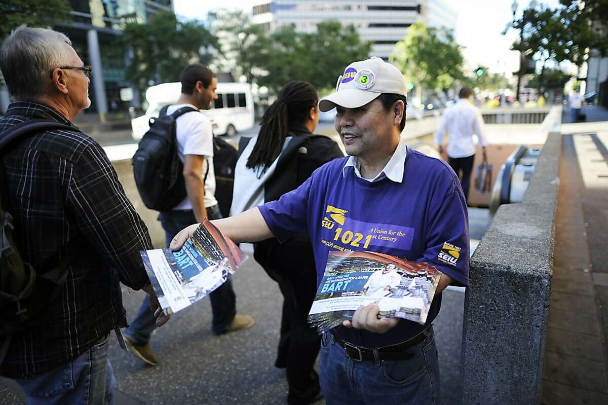 SEIU member and Bart electrician Kenny Fong hands out informational fliers to passengers in front of the 12th St. City Center Bart station in downtown Oakland, CA Thursday June 27th, 2013.