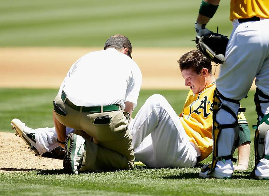Trainer Nick Paparesta tends to Jarrod Parker after he fell to the ground with a hamstring injury on a fourth-inning pitch. Photo: Ezra Shaw, Getty Images