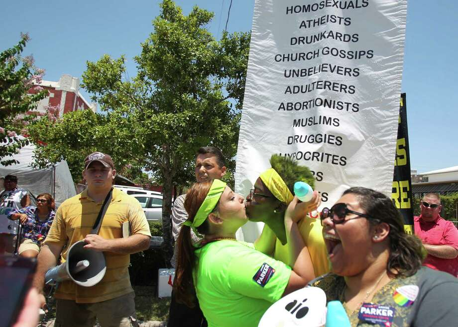 Andrea Trevino and C.J. Tate kiss in front of demonstrators Chris LePelley and Victor Persinger along Westheimer near the route of Saturday's Houston Pride Festival in Houston's Montrose neighborhood. Photo: Mayra Beltran, Staff / © 2013 Houston Chronicle