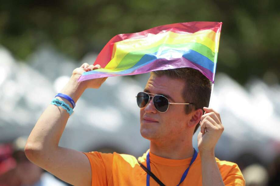HoustonRyan Tyler Ash finds a rainbow flag can also be used for  shade while enjoying entertainment at the festival. Photo: Mayra Beltran, Staff / © 2013 Houston Chronicle