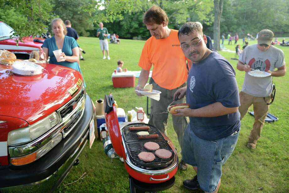 Mark Lopes, a firefighter with Mill Plain Engine 12, cooks burgers and hot dogs on the grill for other members of his department before the July 4th fireworks display at Candlewood Lake in Danbury, Conn. on Saturday, June 29, 2013. Photo: Tyler Sizemore / The News-Times