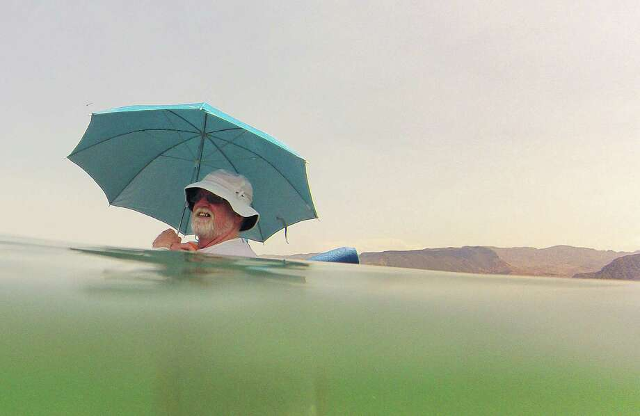 Mike Bouse of Henderson, Nev., shades himself with an umbrella as he floats in the waters along Boulder Beach at Lake Mead, Saturday, June 29, 2013 near Boulder City, Nev. Bouse and his wife planned to spend most of the day in and out of the water to escape the heat in the Las Vegas area where Saturday's daytime high was expected to reach 117 degrees, the city's all-time high. It was 108 at noon Saturday in Sin City. (AP Photo/Julie Jacobson) ORG XMIT: NVJJ104 Photo: Julie Jacobson / AP