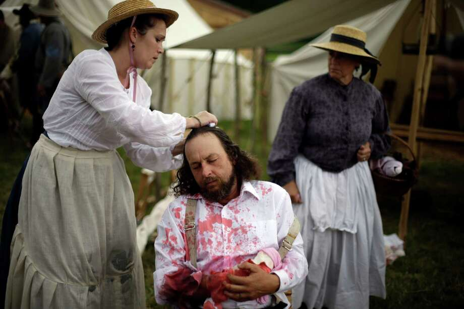 A Floridian portraying a wounded soldier from the 1st N.C. Infantry takes part of demonstration of a Confederate field hospital during ongoing activities commemorating the 150th anniversary of the Battle of Gettysburg, Friday, June 28, 2013, at the Daniel Lady Farm in Gettysburg, Pa.  Union forces turned away a Confederate advance in the pivotal battle of the Civil War fought July 1-3, 1863, which was also the war's bloodiest conflict with more than 51,000 casualties. Photo: Matt Rourke, Associated Press / AP