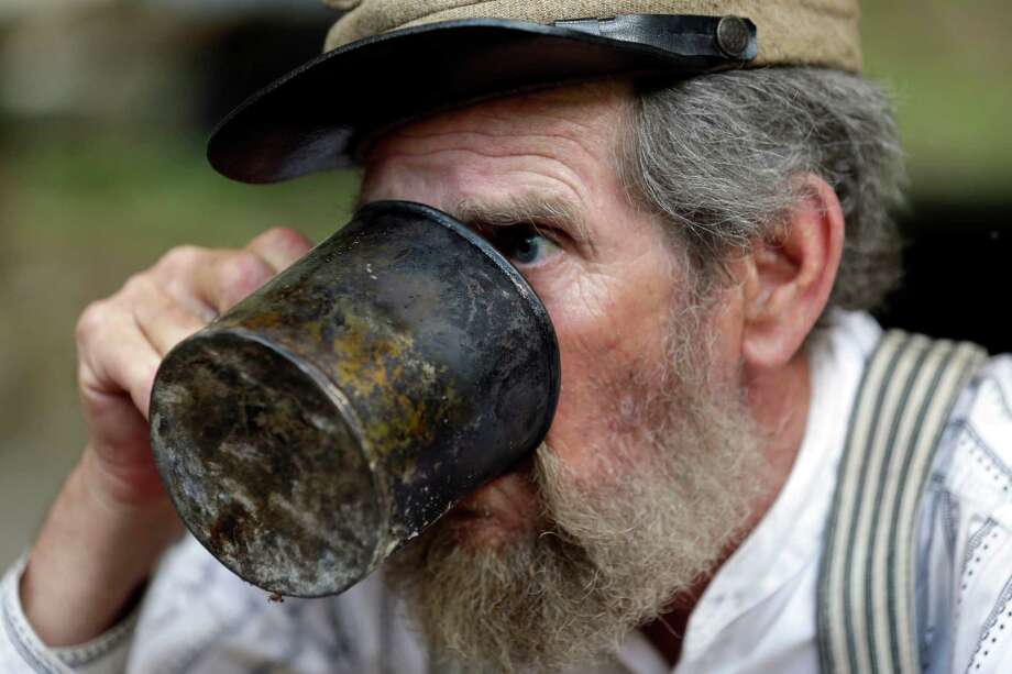 David Dunn of Dallas, with the Confederate 9th Texas Infantry, takes a drink from his mug during ongoing activities commemorating the 150th anniversary of the Battle of Gettysburg, Thursday, June 27, 2013, in Gettysburg, Pa. Photo: Matt Rourke, Associated Press / AP