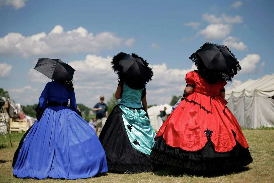 "Reenactors portraying ""ladies of the evening"" walk through a shopping area during ongoing activities commemorating the 150th anniversary of the Battle of Gettysburg, Saturday, June 29, 2013, at Bushey Farm in Gettysburg, Pa. Photo: Matt Rourke, Associated Press / AP"