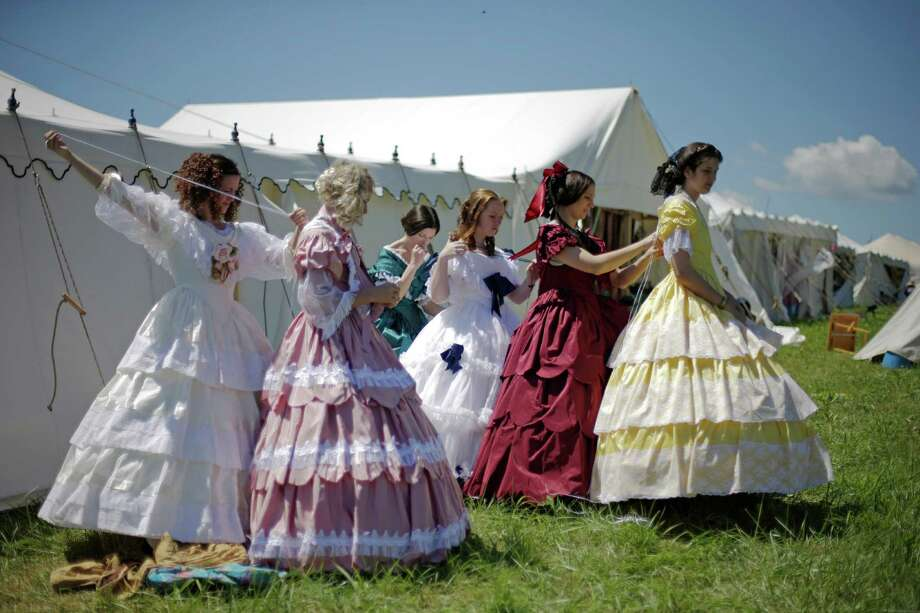 Women in Civil War era ball gowns help each other undress during ongoing activities commemorating the 150th anniversary of the Battle of Gettysburg, Saturday, June 29, 2013, at Bushey Farm in Gettysburg, Pa.  Union forces turned away a Confederate advance in the pivotal battle of the Civil War fought July 1-3, 1863, which was also the war's bloodiest conflict with more than 51,000 casualties. Photo: Matt Rourke, Associated Press / AP