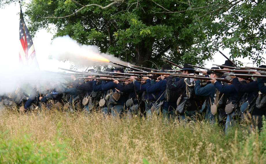 "The 24th Michigan ""Iron Brigade"" fires a volley at the Confederate Army during ongoing activities commemorating the 150th anniversary of the Battle of Gettysburg, Friday, June 28, 2013, at  at Bushey Farm in Gettysburg, Pa.  Union forces turned away a Confederate advance in the pivotal battle of the Civil War fought July 1-3, 1863, which was also the war's bloodiest conflict with more than 51,000 casualties. Photo: Jeremy Long, Associated Press / Lebanon Daily News"