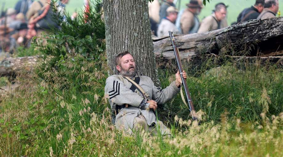 2nd Sgt. Donnie Mattingly with the 4th Kentucky Co. F lays mortally wounded at the base of the tree during ongoing activities commemorating the 150th anniversary of the Battle of Gettysburg, Friday, June 28, 2013, at  at Bushey Farm in Gettysburg, Pa.  Union forces turned away a Confederate advance in the pivotal battle of the Civil War fought July 1-3, 1863, which was also the war's bloodiest conflict with more than 51,000 casualties. Photo: Jeremy Long, Associated Press / Lebanon Daily News