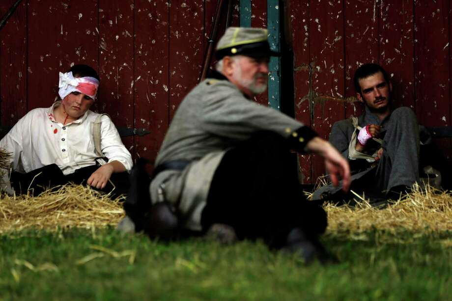 Floridians portray wounded soldiers from the 1st N.C. Infantry as part of demonstration of a Confederate field hospital during ongoing activities commemorating the 150th anniversary of the Battle of Gettysburg, Friday, June 28, 2013, at the Daniel Lady Farm in Gettysburg, Pa. Photo: Matt Rourke, Associated Press / AP