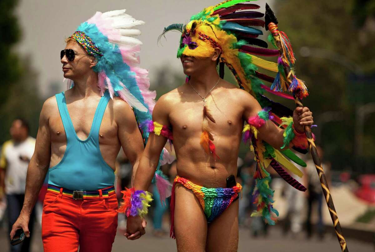 Men in costume hold hands as they make their way to the annual Gay Pride Parade in Mexico City, Saturday, June 29, 2013. (AP Photo/Ivan Pierre Aguirre)