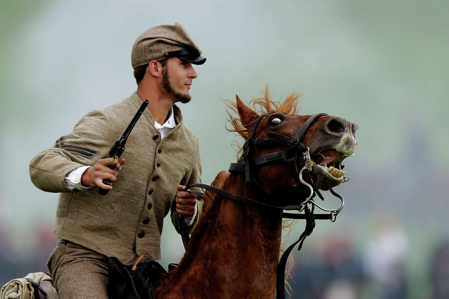 A mounted Confederate reenactor takes part in a demonstration of a battle during ongoing activities commemorating the 150th anniversary of the Battle of Gettysburg, Friday, June 28, 2013, at  at Bushey Farm in Gettysburg, Pa. Photo: Matt Rourke, Associated Press / AP
