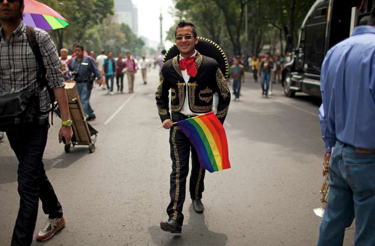 A man wearing a Mexican mariachi costume and carrying a gay pride flag makes his way to the annual Gay Pride Parade in Mexico City, Saturday, June 29, 2013. (AP Photo/Ivan Pierre Aguirre)
