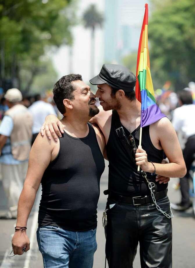 Two men kiss during the 35th Gay Pride Parade along Reforma Avenue in Mexico City on June 29, 2013. AFP PHOTO/Alfredo EstrellaALFREDO ESTRELLA/AFP/Getty Images Photo: ALFREDO ESTRELLA, AFP/Getty Images / AFP