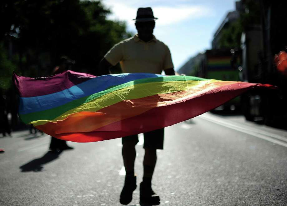 A participant waves a rainbow flag during the Gay and Lesbian Pride parade in Barcelona on June 29, 2013. AFP PHOTO / JOSEP LAGOJOSEP LAGO/AFP/Getty Images Photo: JOSEP LAGO, AFP/Getty Images / AFP
