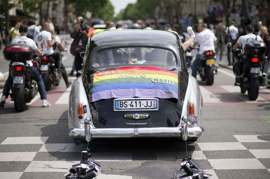 A decorated car and motocyclists parade during the homosexual, lesbian, bisexual and transgender (HLBT) visibility march, the Gay Pride, on June 29, 2013 in Paris. AFP PHOTO / LIONEL BONAVENTURELIONEL BONAVENTURE/AFP/Getty Images Photo: LIONEL BONAVENTURE, AFP/Getty Images / AFP
