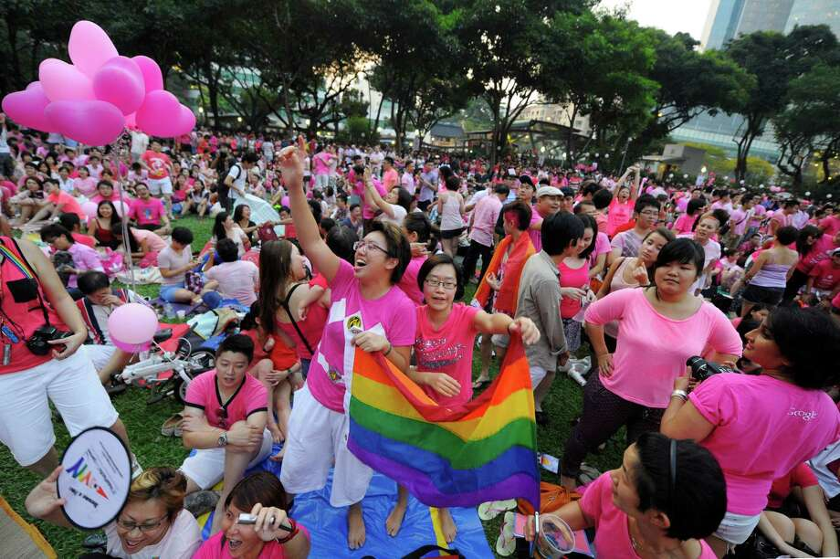 "Two women cheer at a rally called the ""Pink Dot"" in support of gay rights in Singapore, Saturday, June 29, 2013. The movement hopes to raise awareness of the impact of the anti-gay law and other gay rights issues like through its public show of support.  (AP Photo/Joseph Nair) Photo: Joseph Nair, Associated Press / AP"