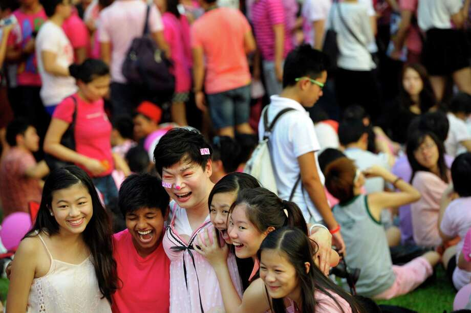 "Girls pose for a picture with a man in a dress, center, at a rally called the ""Pink Dot"" in support of gay rights in Singapore's speakers corner on Saturday, June 29, 2013. The movement hopes to raise awareness of the impact of the anti-gay law and other gay rights issues like through its public show of support. (AP Photo/Joseph Nair) Photo: Joseph Nair, Associated Press / AP"