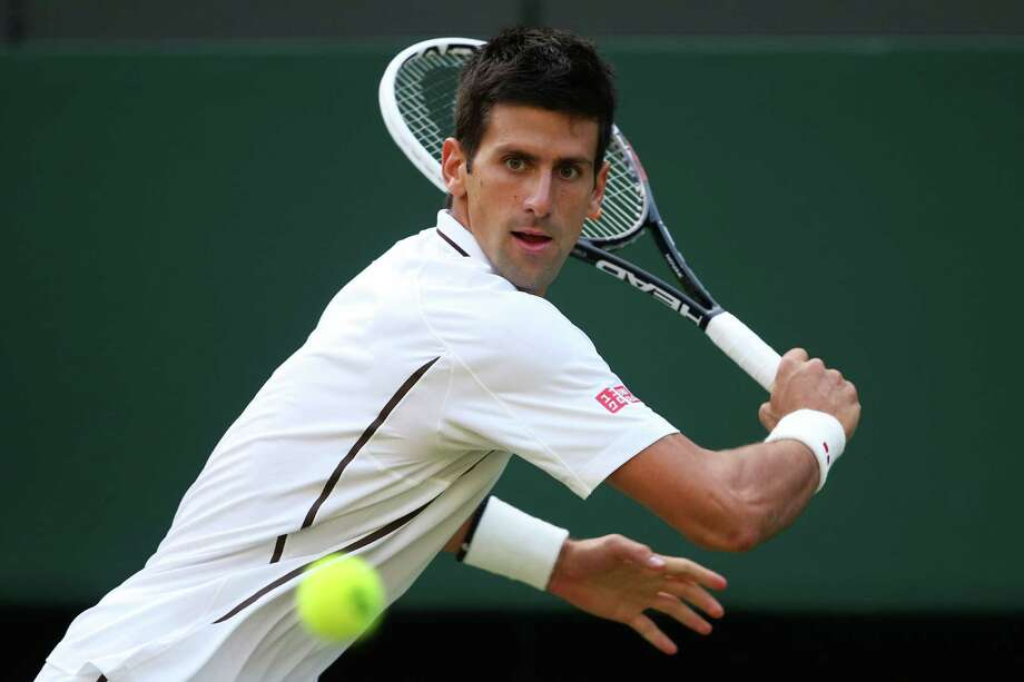Top seed Novak Djokovic of Serbia concentrates on his backhand during his straight-sets victory over Jeremy Chardy of France on Saturday at Wimbledon. Djokovic committed only three unforced errors. Photo: Clive Brunskill, Staff / 2013 Getty Images