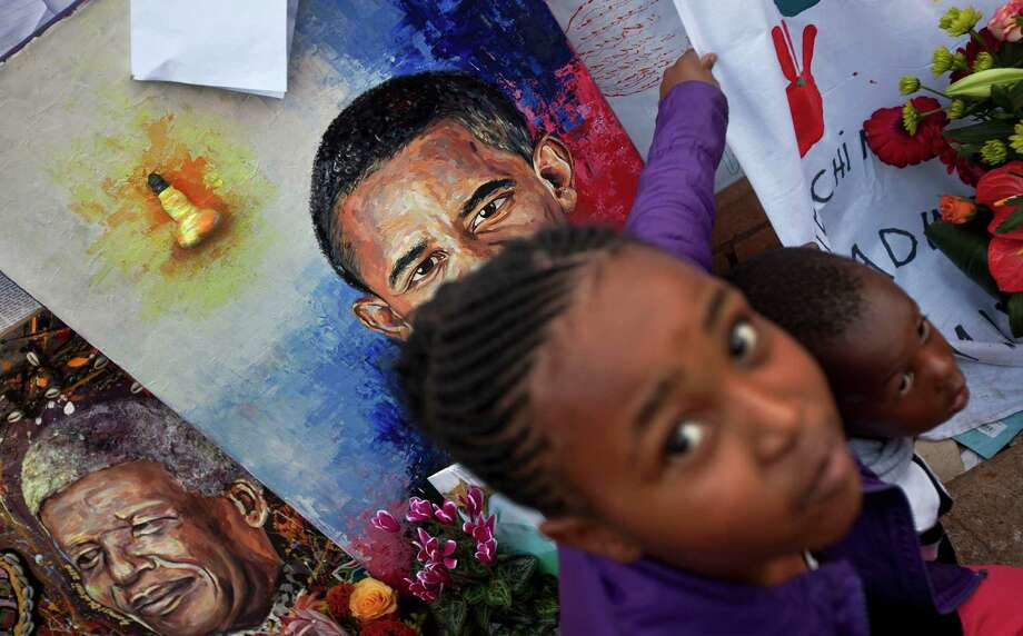 Children get their photograph taken next to paintings of President Barack Obama and Nelson Mandela in Pretoria, South Africa. Photo: Ben Curtis, STF / AP
