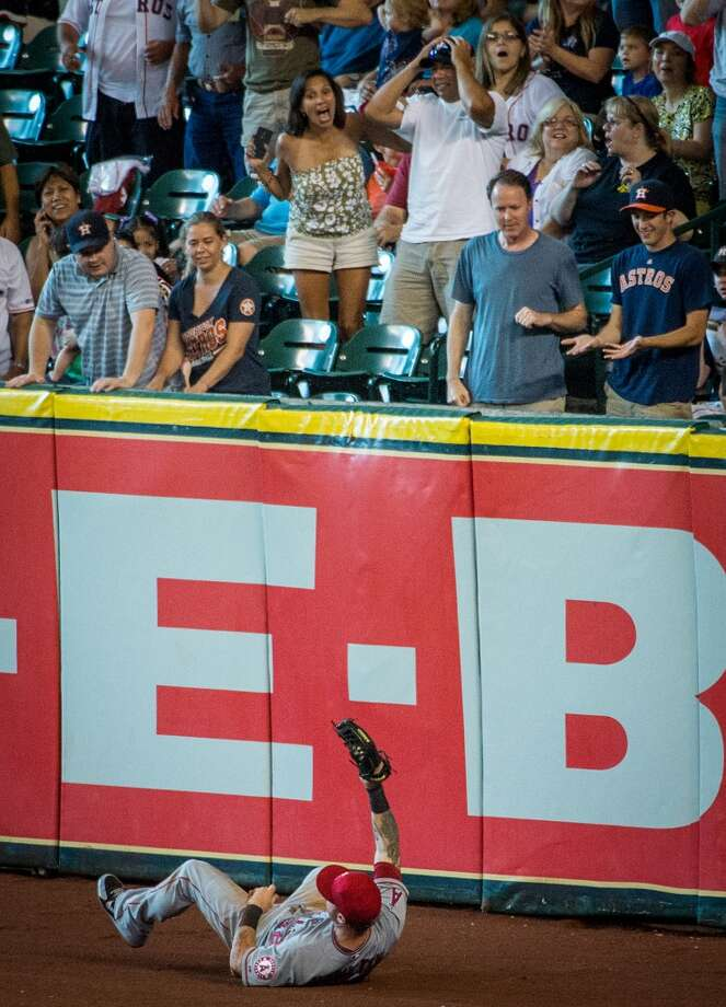Fans react as Angels right fielder Josh Hamilton holds up the ball after making a leaping catch over the wall to rob Matt Dominguez of a homer.