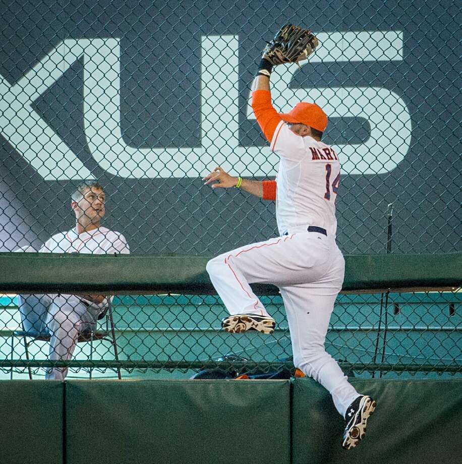 Astros right fielder J.D. Martinez crashes into the fence as he makes a leaping catch on a ball hit by Angels third baseman Alberto Callaspo during the sixth inning.