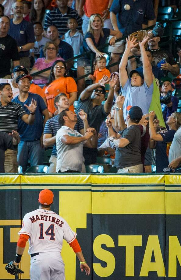 Astros right fielder J.D. Martinez watches as fans try to catch a home run by Howie Kendrick during the fifth inning.