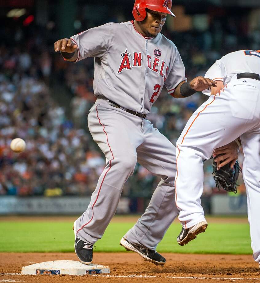 Angels shortstop Erick Aybar gets back to first as the ball gets away from Astros first baseman Brett Wallace during the third inning.
