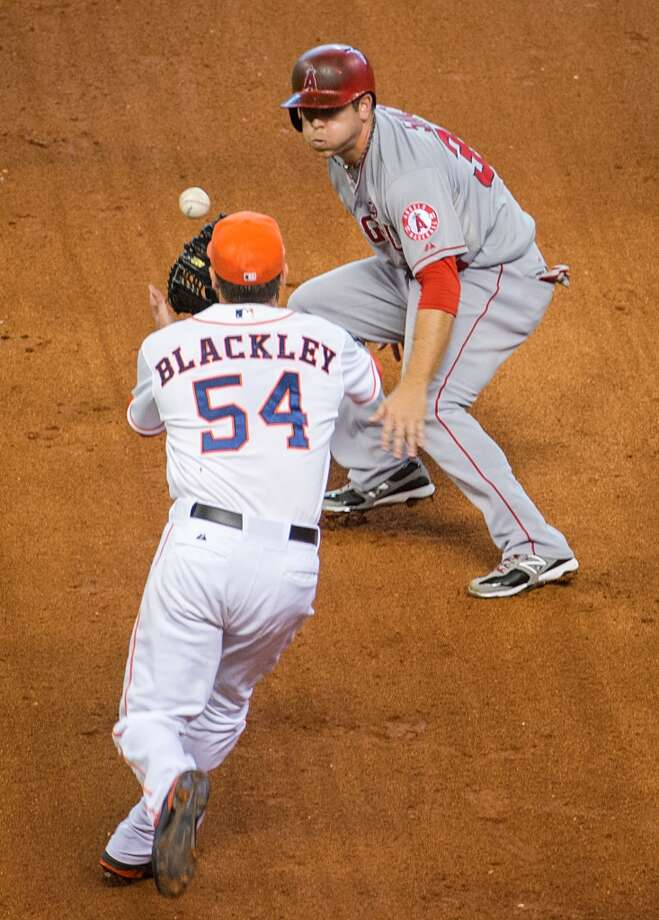 Angels left fielder J.B. Shuck is cased by Astros relief pitcher Travis Blackley as he is caught in a rundown.