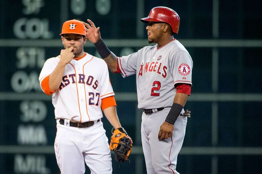 Angels shortstop Erick Aybar pats Astros second baseman Jose Altuve on the head after advancing to second base on throwing error by Jake Elmore  during the third inning.