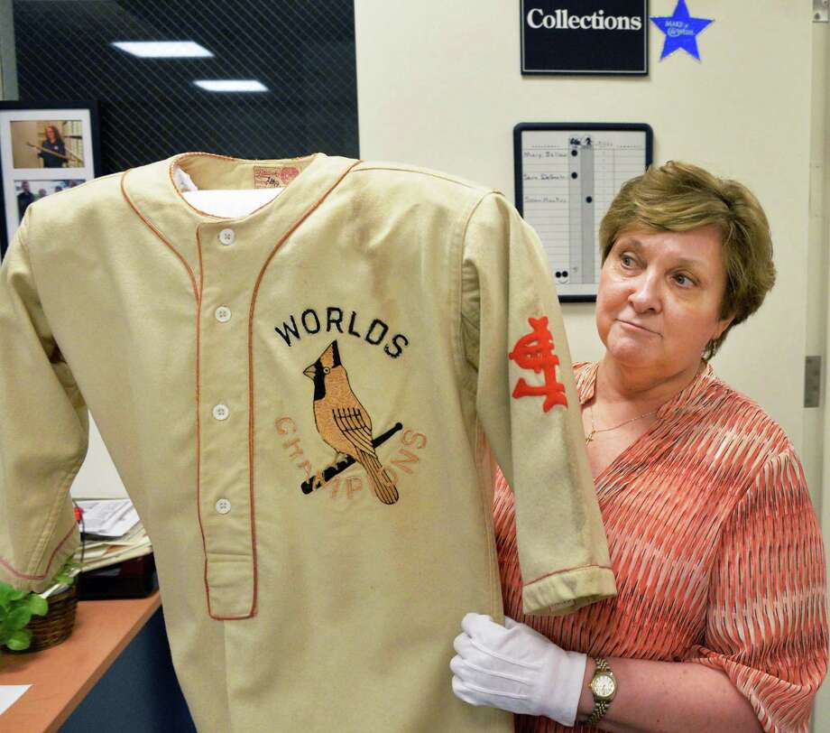 Assistant registrar Mary Bellew with Grover Cleveland Alexander's 1927 World Championship jersey at the National Baseball Hall of Fame and Museum in Cooperstown, NY, Tuesday June 25, 2013.  (John Carl D'Annibale / Times Union) Photo: John Carl D'Annibale / 00022940A