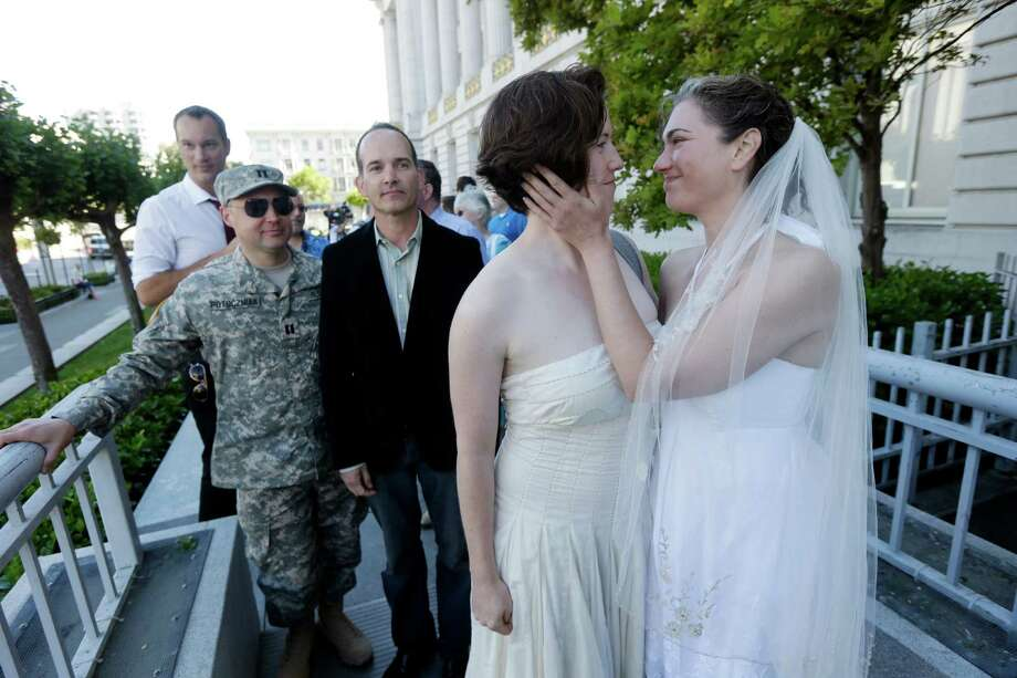 From left, Army Capt. Michael Potoczniak, Todd Saunders, in black, Elizabeth Carey and Cynthia Wides, with bridal gown, stand in line outside City Hall on Saturday waiting to be married in San Francisco. Photo: Marcio Jose Sanchez, STF / AP