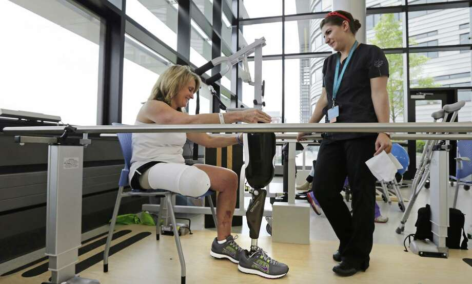 Boston Marathon bombing survivor Roseann Sdoia talks with physical therapist Dara Casparian on June 20 as she prepares to fit her prosthetic leg at the Spaulding Rehabilitation Hospital in Boston. Sdoia went back to the hospital to learn to walk with her new leg. Photo: Charles Krupa / Associated Press